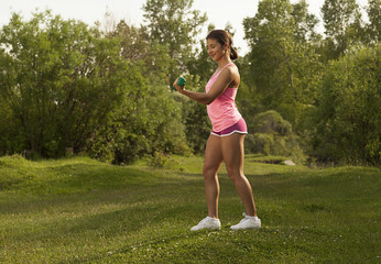 young beautiful athletic girl engaged in fitness in the park