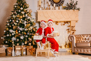 two boys in Santa costumes are sitting under the tree