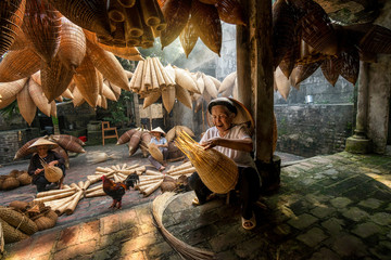 Old Vietnamese female craftsman making the traditional bamboo fish trap or weave at the old traditional house in Thu sy trade village, Hung Yen, Vietnam, traditional artist concept Wall mural