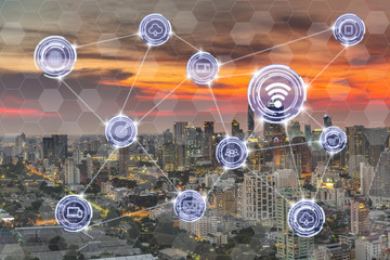 Wireless communication connecting of smart city Internet of Things Technology over the modern cityscape at evening background, technology business IOT concept