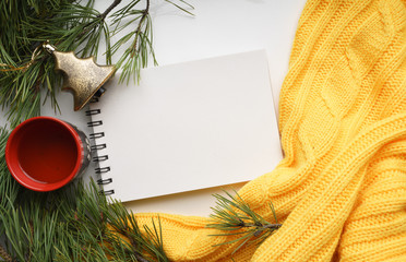 Christmas background with a Cup  of tea, a notebook, branches of pine with large needles and a yellow sweater. Top view close-up