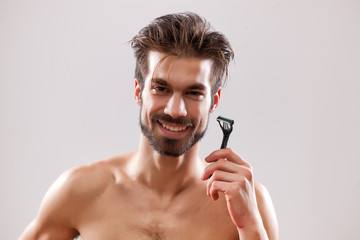 Young man is holding razor and he is going to shave his beard.