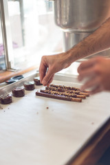 Confectioner decorating chocolate sticks
