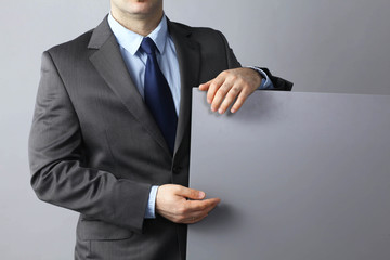 Businessman standing and holding a blank board
