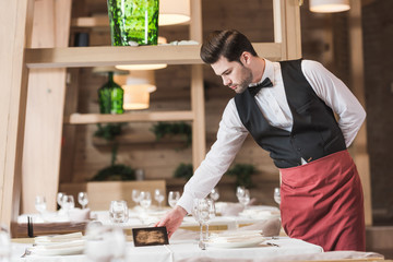 Waiter putting reserved sign