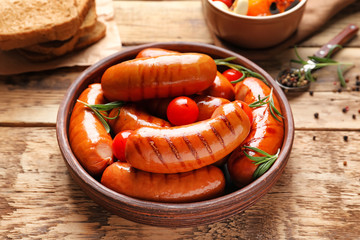 Grilled sausages served with tomatoes on plate on kitchen table