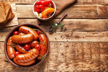 Composition with grilled sausages and vegetables on wooden background