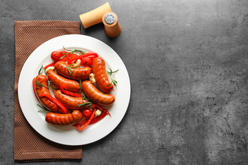 Grilled sausages served with garlic and pepper on plate