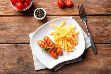 Plate with delicious grilled sausages and french fries on wooden background
