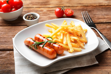 Plate with delicious grilled sausages and french fries on table