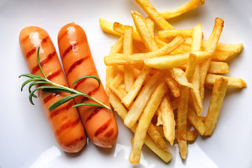 Plate with delicious grilled sausages and french fries, close up