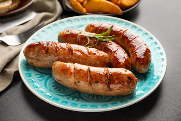 Plate with delicious grilled sausages on table