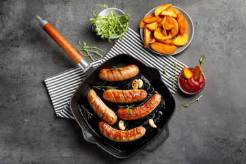 Grill pan with delicious grilled sausages on grey background