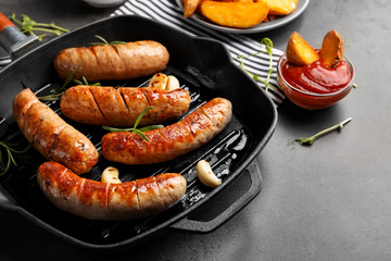 Grill pan with delicious grilled sausages on table