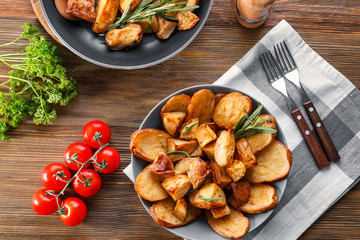 Composition with plate of baked rosemary potatoes on table