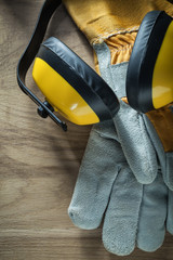 Earmuffs pair of safety gloves on wooden board