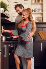 Image of happy loving woman and man preparing food in kitchen