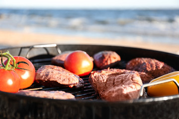 Tasty steaks and vegetables on barbecue grill, closeup