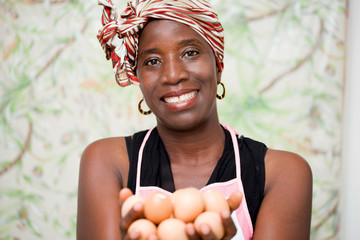 young smiling woman holding eggs in the hand