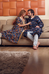 Image of woman and man in home clothes hugging on sofa