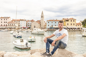 young man resting chilling on the rocks of the harbor of colorful old istria city Fazana - Croatia