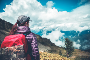 Photo from back of girl with backpack on background of mountains