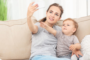 Mother with baby boy taking selfie on sofa at home