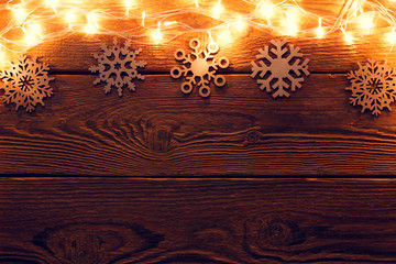 Picture of wooden surface with burning garland on top, snowflakes.