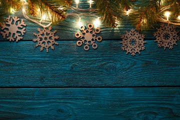 Image of blue wooden surface with burning New Year garland, snowflakes.