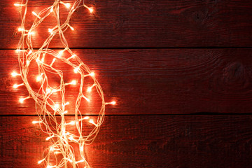 Image of New Year's wooden red background with burning garland around perimeter.
