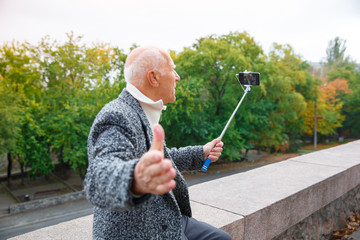 Close-up of an elderly man in a gray jacket and white shirt with a monopod in his hands, shoots a video.
