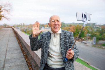 Close-up of an elderly man in a gray jacket with a monopod in his hands, shoots a video