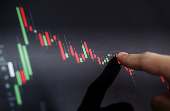 Close-up finger pointing on stock exchange chart