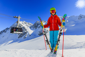 Wall Mural - Portrait of happy young girl on the snow with ski in winter time, ski slope and cable car in background.