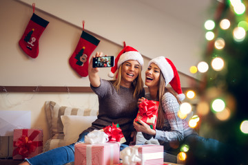 Two adorable excited girlfriends with Santa hat sitting on the bed for Christmas holidays one next to another and taking a selfie while laughing on laud.