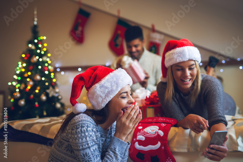 5fdd1001b Two gorgeous attractive girls with Santa hats laughing at mobile ...