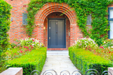 Front door of an English cottage decorated with garden plants and flowers