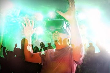 Young man wearing virtual reality glasses enjoying concert with smartphone with VR headset. Virtual reality concept.