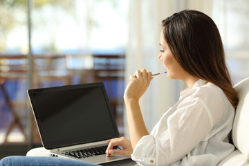 Woman thinking using a laptop with blank screen