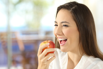 Woman eating an apple at home