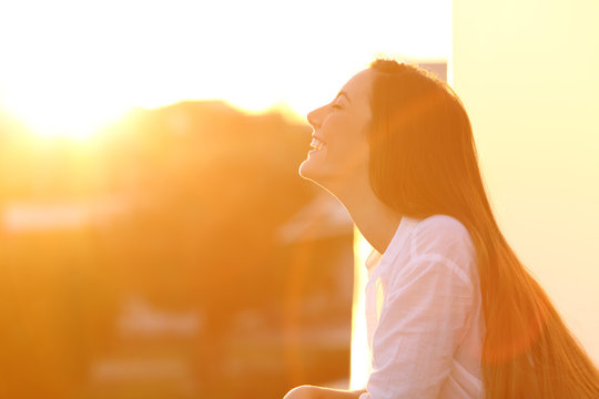 Woman breathing at sunset in a balcony
