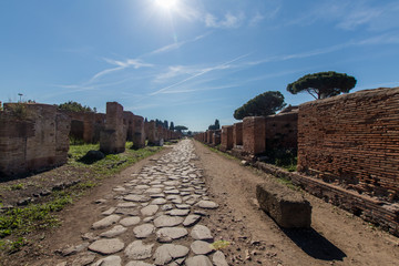 Ancient Roman road paved with stones for carriage. Decumano maximum in Ostia ancient 2nd century. Sun, sea pines and Roman ruins in the background