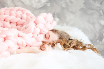Young woman sleeping under warm peach color throw blanket