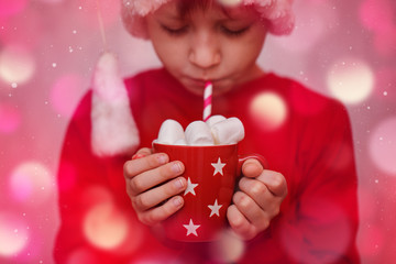 Child hands holding red cup of hot cocoa or chocolate with marshmallow. Christmas concept