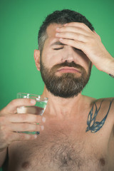 headache of man with beard on face drink water from glass
