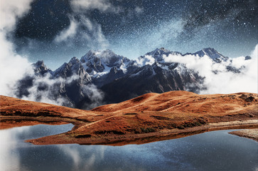 Fantastic starry sky on mountain lake Koruldi. Picturesque night Upper Svaneti, Georgia Europe. Caucasus mountains