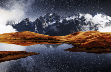 Fantastic starry sky on mountain lake Koruldi. Picturesque night Upper Svaneti, Georgia Europe. Caucasus mountains