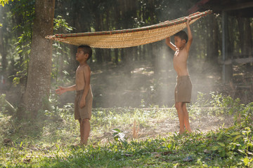 Two brothers standing by with a bamboo boat on a head in rural Thailand.