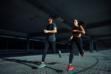 Young sports couple running in the urban environment