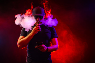 Men with beard in sunglasses vaping and releases a cloud of vapor. vaping man holding a mod.